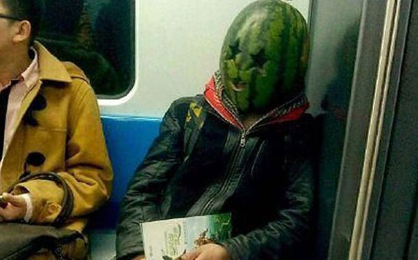 mysterious man rides the train with a watermelon on his