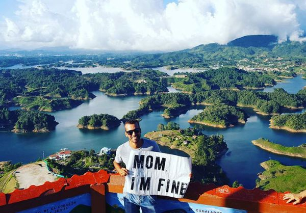 Guy Uses Sign To Assure His Mom He's Okay While Traveling Around The World