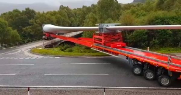 Truck Driver Carrying 200-Foot-Long Turbine Blade Makes Extremely Tight Turn Onto Bridge